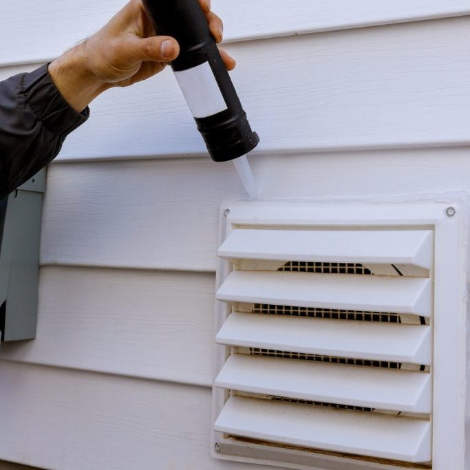 applying silicone on plastic exhaust fan on the wall outside siding trim
